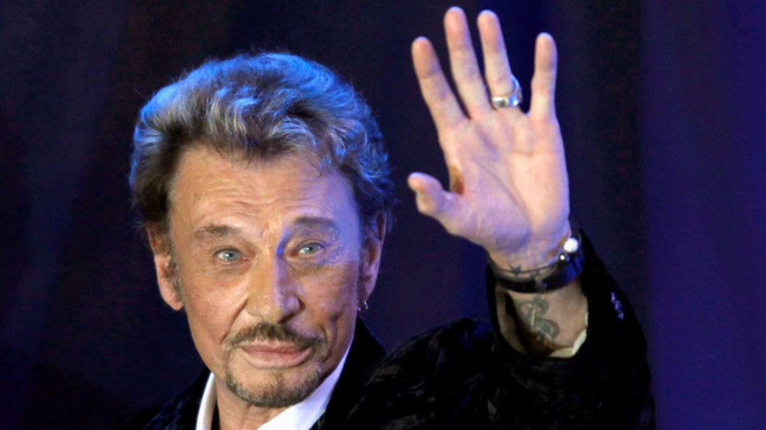 "FILE PHOTO: French singer Johnny Hallyday waves to fans attending a ceremony to promote his new album ""Jamais seul"" (Never alone) at the Virgin Megastore in Paris early March 28, 2011. REUTERS/Charles Platiau/File Photo - RC1D5894A250"